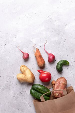 Set of ripe ugly vegetables scattered in diagonal out of paper bag on grey concrete background.