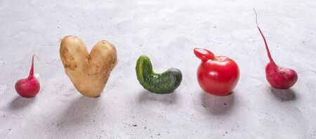 Five ugly vegetables are standing in row on grey concrete background.
