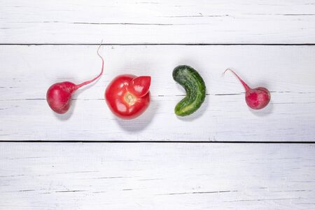 Four ugly vegetables laid out in row on white wooden background.