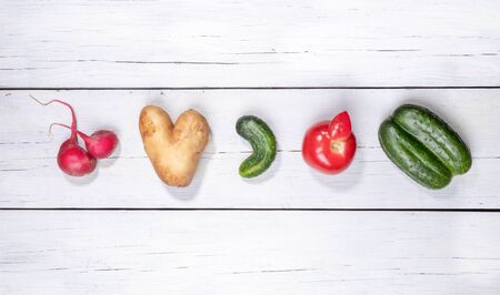 Set of five ugly vegetables: potato, tomato, cucumber and radish laid out in row on white wooden background.