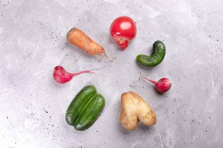 Set of ugly vegetables laid out in circle on concrete background.