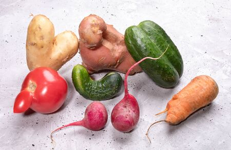 Pile of ripe ugly vegetables on concrete background.