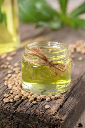 Hemp oil in glass jar and grains of cannabis on old wooden board, bottle with oil and leaves are blurred.