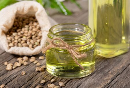 Close-up hemp oil in glass jar and bottle with cannabis grains in sack on wooden board. Zdjęcie Seryjne