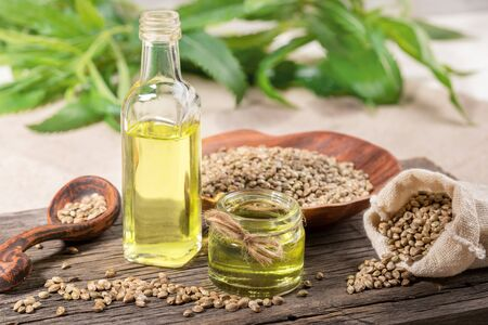 Hemp oil in glass jar and bottle, seeds in ceramic plate and spoon and in sack on wooden board, with leaves on backdrop. Zdjęcie Seryjne