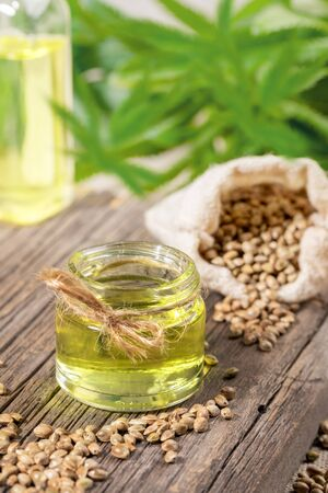 Hemp products: oil in glass jar in the foreground, bottle, cannabis grains in sack and leaves on backdrop. Zdjęcie Seryjne