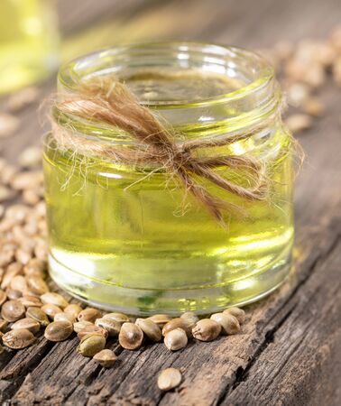 Hemp oil in glass jar and grains of cannabis on background of old wooden boards close-up. Zdjęcie Seryjne