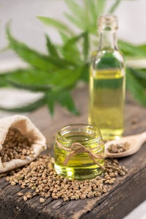 Hemp oil in two glass jar and bottle with grain in the sack on wooden board with leaves of cannabis on background.