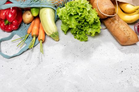 Fresh farm vegetables in string bag and baguettes and bananas in paper bag on concrete background. Imagens
