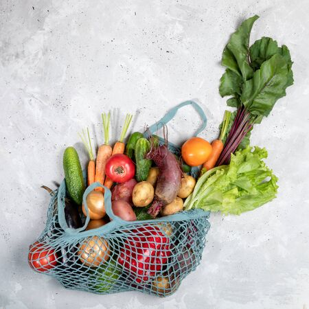 Top view of string bag with fresh farm vegetables on grey concrete background. Imagens