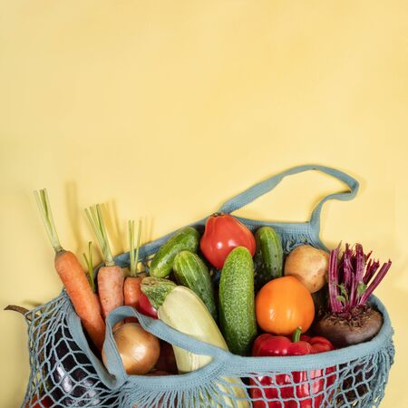 Close-up string bag full of fresh farm vegetables on yellow background with copy space. Imagens - 132067772