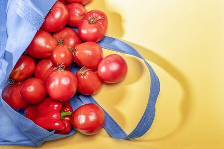 Fresh red ripe farm tomatos spilling out of blue non-woven shopping bag on yellow background.