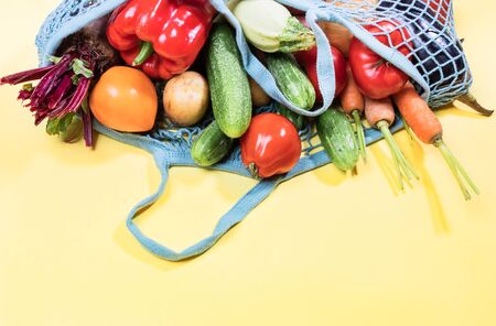 Blue mesh shopping bag full of fresh farm vegetables is lying on top of yellow background with copy space on bottom.