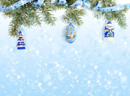 Xmas decorations in blue color. Festive Christmas border - green fir branches, covered with snow and decorated with shiny ribbon with starlets, christmas toys on blue background with snow and copy space.