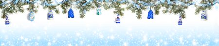 Xmas background in blue color. Extra wide festive Christmas border - green fir branches, covered with snow and decorated with shiny ribbon with starlets, christmas toys on gradient blue background with snow and stars and copy space.