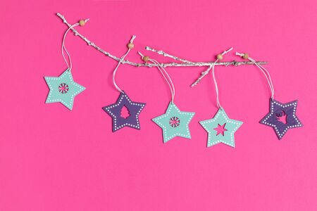 Christmas toys turquoise and purple painted wooden stars on white twig on bright pink background. Imagens