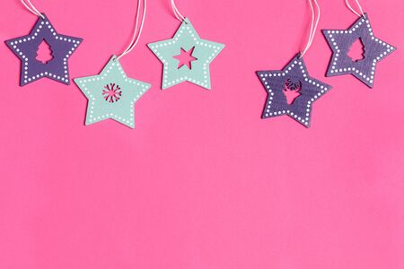 Xmas toys turquoise and purple wooden stars with carved in them deer, Christmas tree, snowflake, starlet on pink. Imagens
