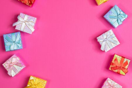 Multicolored shiny gift boxes with ribbons and bows on bright pink background. Festive flat lay layout of presents. Zdjęcie Seryjne