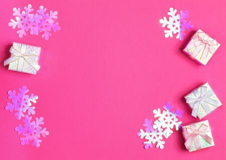 Shiny gift boxes with ribbons and bows and iridescent plastic purple snowflakes on pink background. Christmas layout.