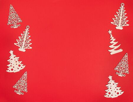 Christmas mockup with two vertical rows of diy wooden decorations christmas trees on red background with copy space. Imagens