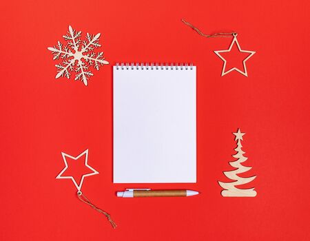 Creative minimal Xmas mockup on red background with diy wooden decorations and white notepad with pen. Flat lay, top view, copy space.