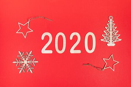 Creative minimal Xmas mockup on red background with wooden decorations: numbers 2020, snowflake, Christmas tree and two stars. Christmas ornaments decorations background. Flat lay, top view. Imagens