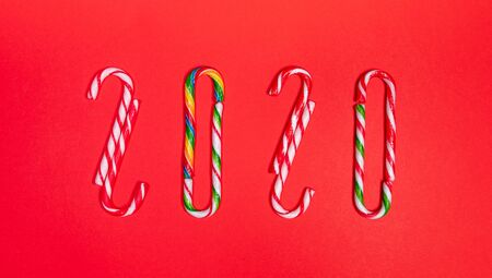 Festive creative christmas banner of numbers 2020 of multicolored traditional xmas candy canes on red background. Flat lay, top view.