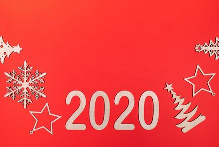 Creative minimal Christmas mockup on red background with wooden Xmas decorations and numbers 2020 with copy space.