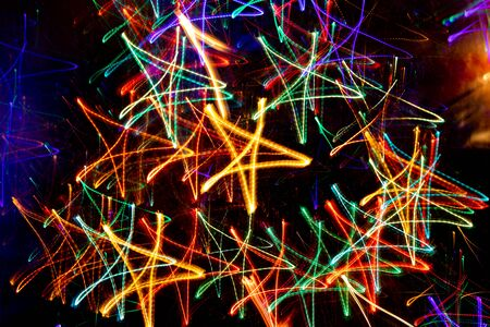Lot of multicolored neon glowing stars on black background. Abstract luminous christmas background.
