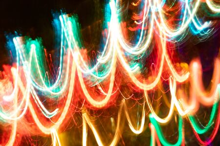 Close-up blurred glowing diagonal neon waves on dark.  Abstract neon luminous background. Photographic effect of long exposure while motion. Stock Photo