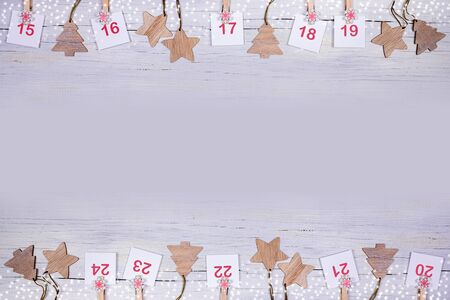 15-24 part of Advent calendar: sheets with numbers and wooden Christmas toys on wooden background toned in lilac. Imagens