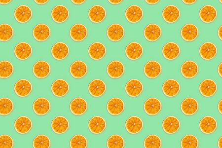 Seamless pattern of handmade dried orange slices on trendy neo mint background 2020.