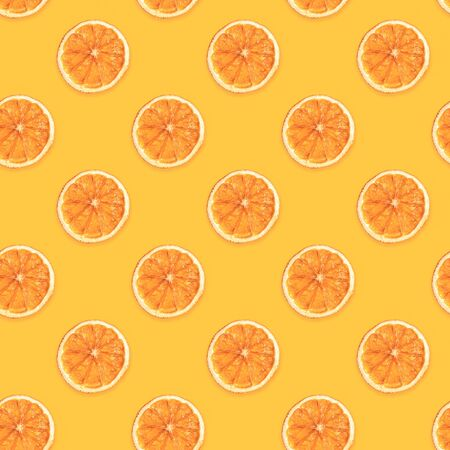 Seamless diagonal pattern of handmade dried orange slices on trendy yellow background.