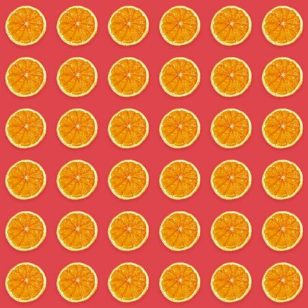 Seamless pattern of handmade dried orange slices on trendy pink background. Imagens