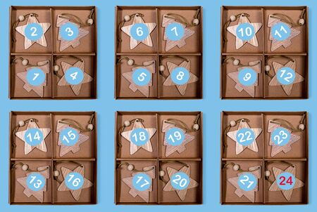 Creative Advent calendar of six paperboard boxes with numbers on wooden Christmas toys on blue background.