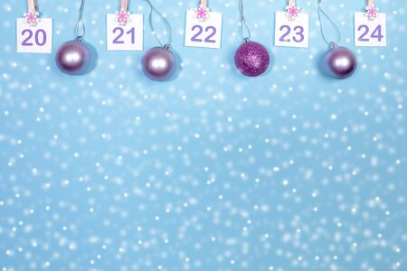 20-24 part of Advent calendar mockup with copy space. Sheets with numbers on clips and christmas balls on snowy blue.