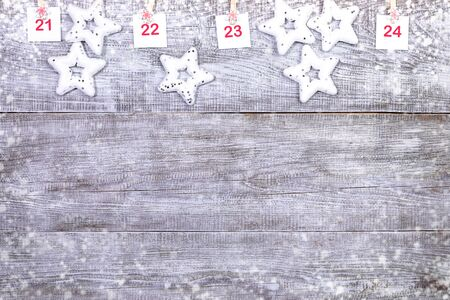 21-24 part of Advent calendar with sheets with numbers and christmas toys stars on white wooden snowy background. Imagens