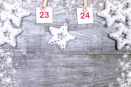 23-24 part of Advent calendar with sheets with numbers and stars on white wooden snowy background with copy space.
