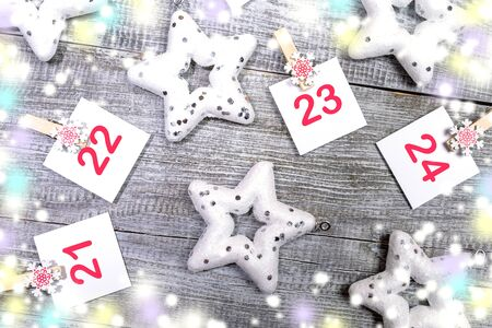 Close-up 21-24 part of Advent calendar: sheets with numbers, stars, blurred color lights on white wooden background. Imagens