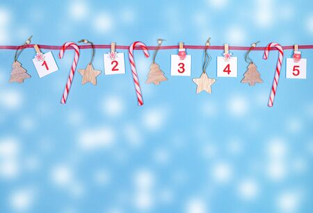 1-5 part of Advent calendar. Sheets with numbers, wooden christmas toys, candy canes on red ribbon on blue background.