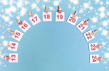 13-24 part of Advent calendar mockup with copy space. Sheets with numbers on clips laid out as arch on snowy blue. Imagens