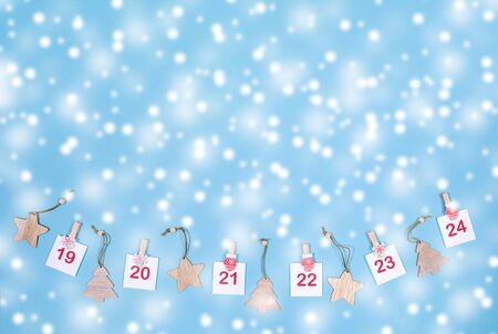 19-24 part of Advent calendar layout. Sheets with numbers on clips and wooden christmas toys on blue snowy background.
