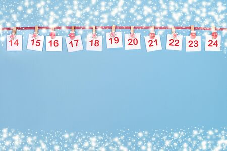 14-24 part of Advent calendar. Sheets with numbers on clips are hanging on red ribbon on blue background.