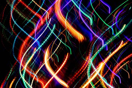 Close-up abstract background of colored chaotic glowing neon wavy stripes on black. Imagens