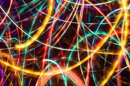 Close-up abstract multicolored chaotic glowing neon stripes on black background. Imagens