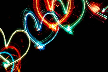 Diagonal row of multicolored neon glowing hearts on black background with copy space. Imagens