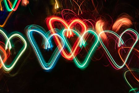 Row of multicolored neon glowing hearts on black background.