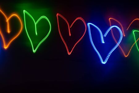 Row of multicolored neon glowing hearts on black background with copy space. Abstract background.