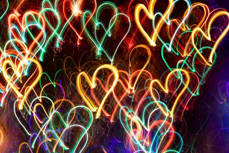 Lot of multicolored neon glowing hearts on dark background. Abstract luminous neon background.