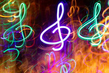 Close-up lot of multicolored neon glowing treble clefs. Abstract  luminous background.